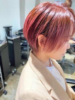 明るいピンク色のつやつやボブヘアの女性