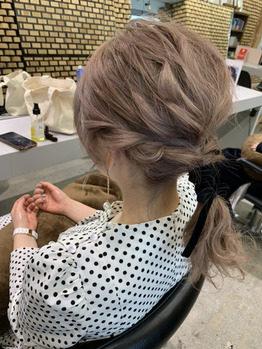 ゆるく髪を編んだ明るい髪色の女性