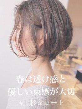 優しい髪色の束感のあるショートヘアの女性