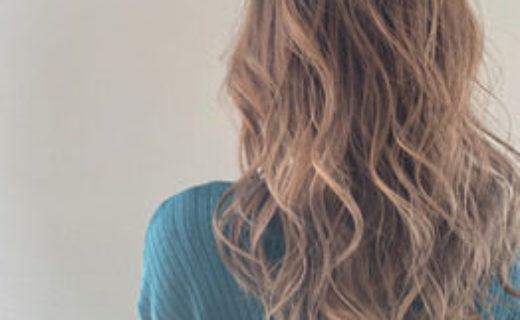 毛先にかけて明るい茶色のグラデーションになったロングヘアの女性