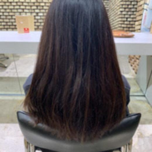 パサついて髪が広がったロングヘアの女性